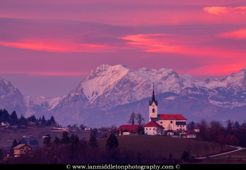 The church of Saint Margaret in Prezganje at sunset, Slovenia. The snow covered Kamnik Alps form a beautiful backdrop.