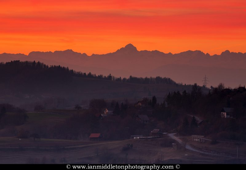 View across the village of Volavje to the Julian Alps and the highest peak, Triglav, at sunset. Volavlje is a small village in the hills east of Ljubljana, Slovenia.