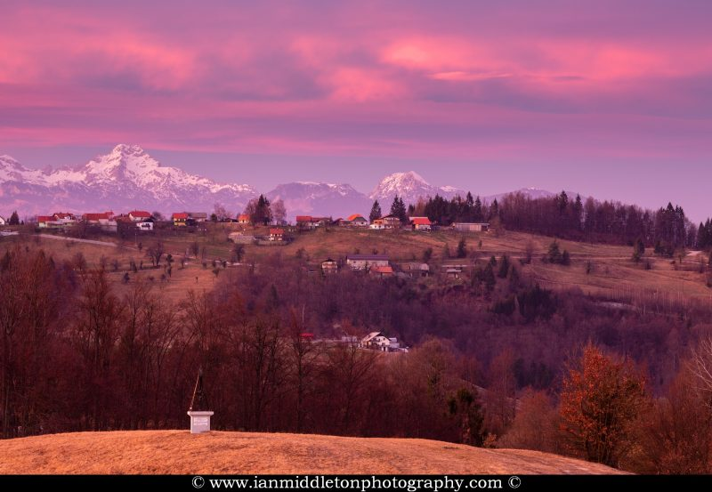 Sunset view across a hill in prezganje to the Kamnik Alps. The shrine on the first hill is to Jesus Christ, built to commemorate the first visit of Pope John Paul the second to Slovenia in 1996.