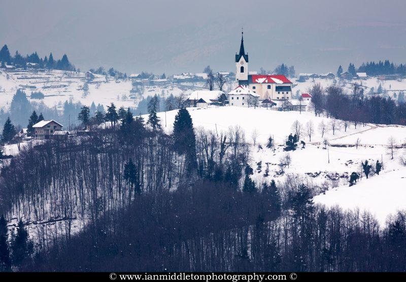 Winter scene of the church of Saint Marjeta in Prezganje in the Jance hills to the east of Ljubljana, Slovenia.