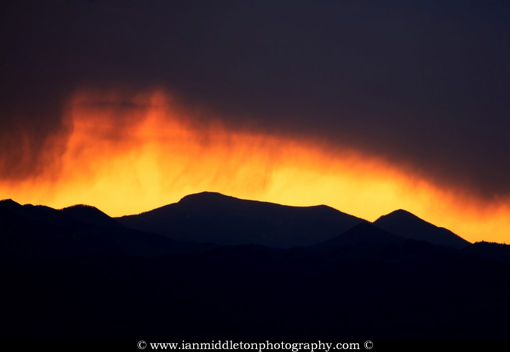 View of the sun setting against a stormy sky over the western mountains of Slovenia. This image was taken from a hill in Tunjice, near Kamnik, where you get a unobstructed view right across to the west.