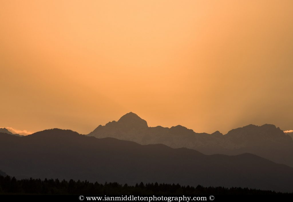 Sun setting behind the jagged peaks of the Julian Alps, Slovenia.