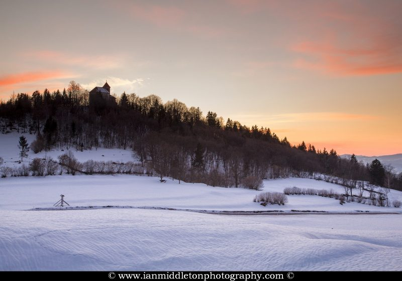 Winter sunset behind the church of Sveti Jozef (Saint Joseph) and the highlands of the Ljubljana Marshland (Ljubljansko Barje), a large area of wetland 160 square kilometres in size.