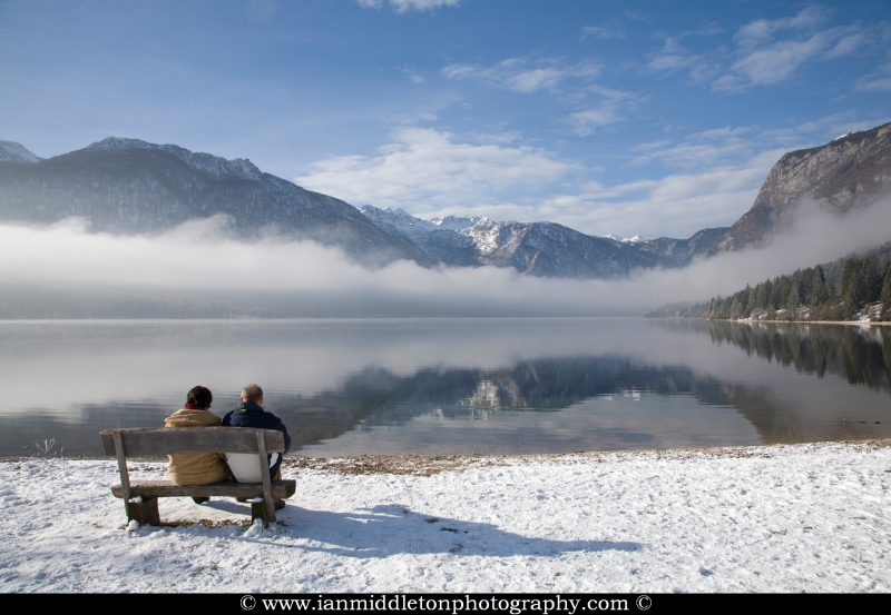 Couple sitting beside Lake Bohinj as the sun burns away the morning mist on New Years Day 2012, Triglav National Park , Slovenia