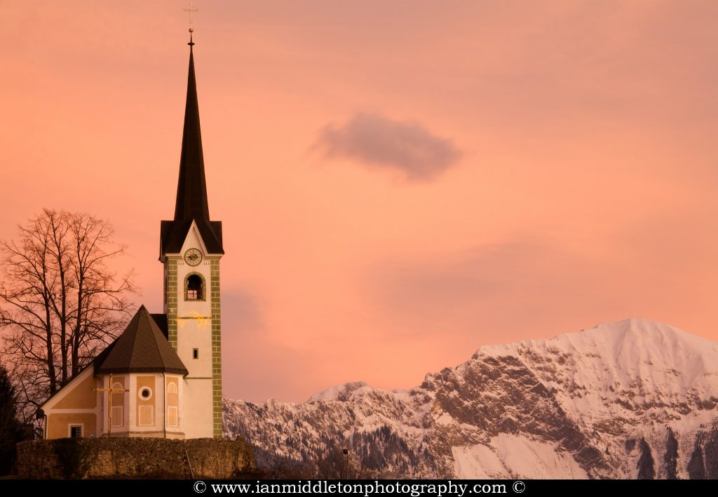 The fortified Tabor church at sunrise. Located in the village of Podbrezje, Gorenjska, with the Kamnik Alps and Karawanke mountains forming a picturesque backdrop. The church is perched upon a rock in the centre of the village and was built some time after 1471 as a fortification into which the locals could escape from Ottoman raids