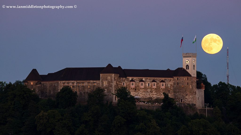 View across the to Ljubljana Castle as the full moon rises behind the tower. Seen from Tivoli Park, Ljubljana, Slovenia.