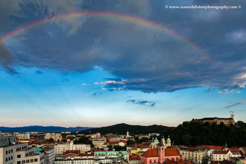 Ljubljana Castle and city centre with a rainbow over, Slovenia. Seen from Neboticnik terrace cafe.