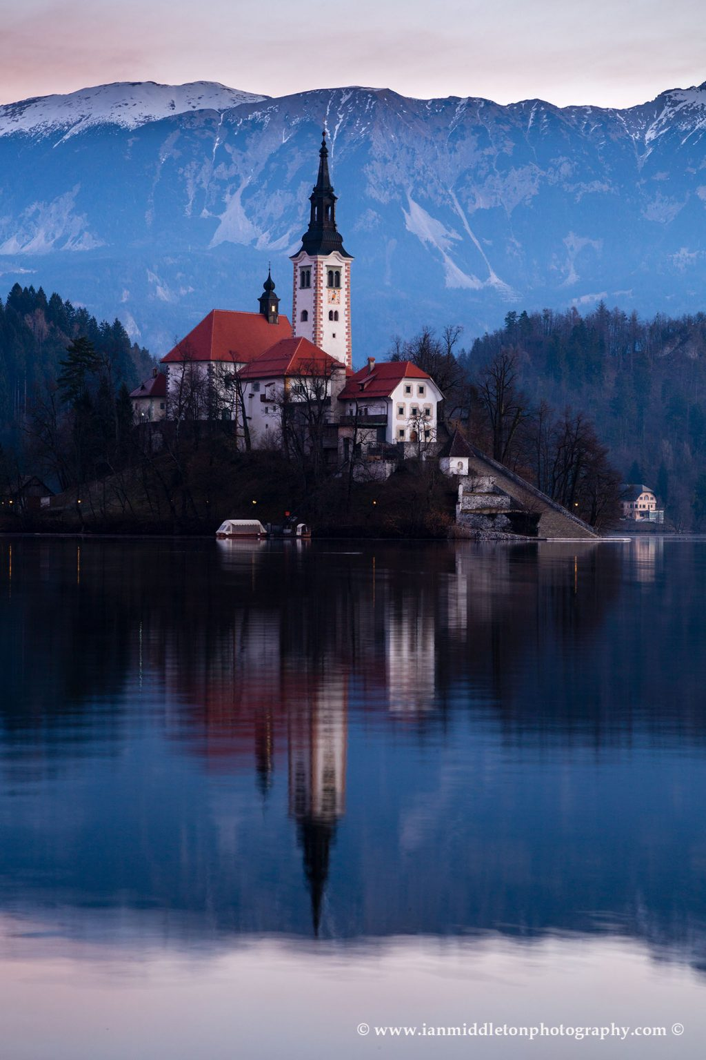 Morning light at Lake Bled's island church with the Karavanke Mountains behind, Slovenia.