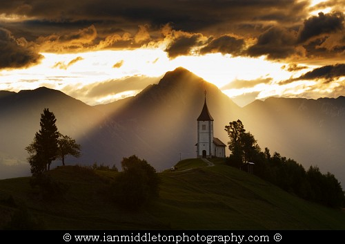 Jamnik church of Saints Primus and Felician at sunrise, perched on a hill on the Jelovica Plateau with the kamnik alps and storzic mountain in the background, Slovenia.
