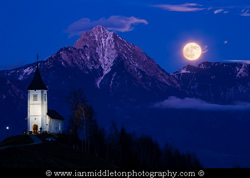 Full moon rising at dusk over Jamnik church of Saints Primus and Felician, perched on a hill on the Jelovica Plateau with the kamnik alps and Storzic mountain in the background, Slovenia.